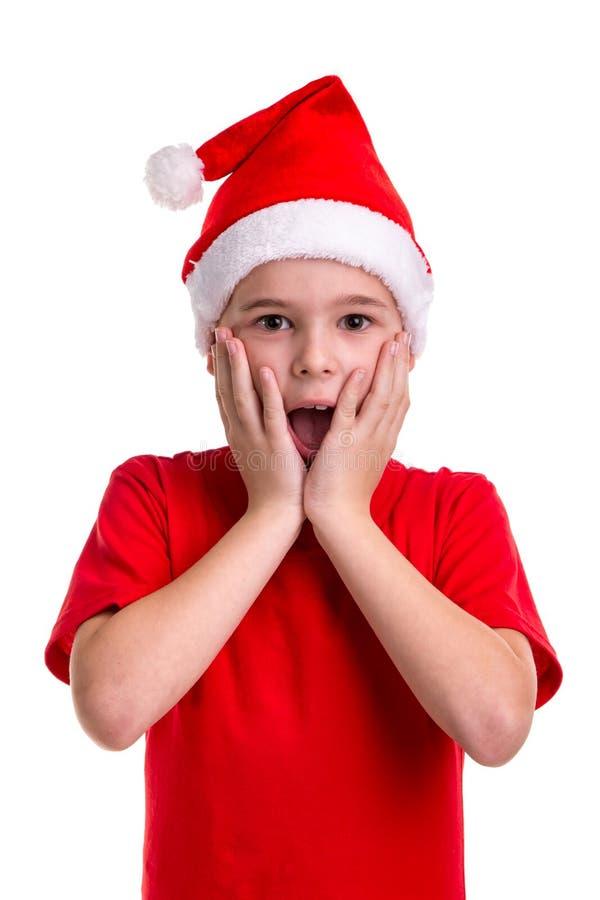 Счастливо изумил мальчика, шляпу santa на его голове Концепция: рождество или С Новым Годом! праздник стоковое изображение rf