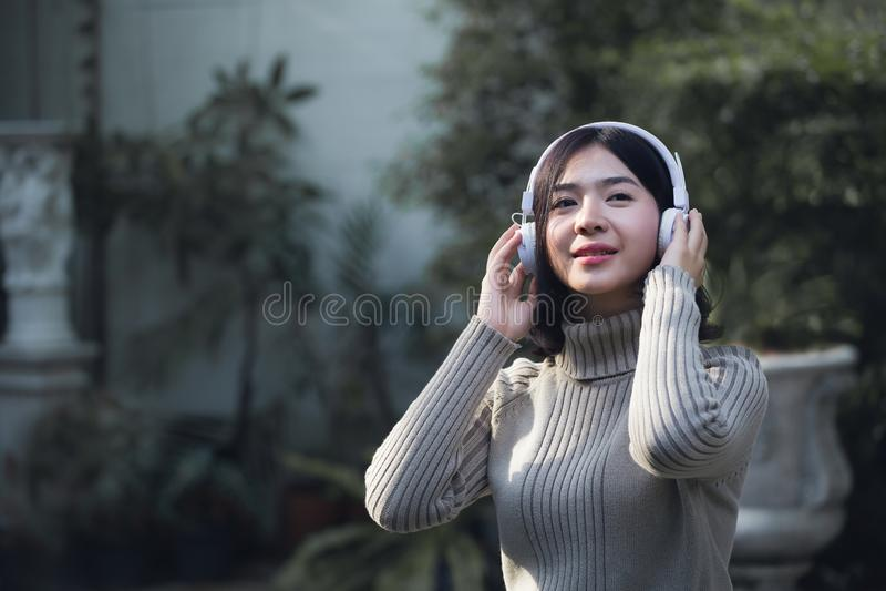 Счастливые азиатские девушки слушают к музыке стоковые фотографии rf