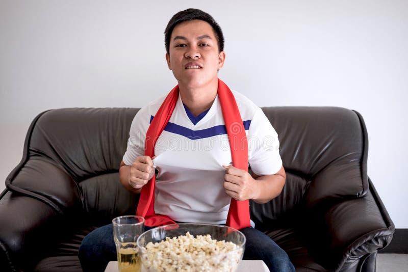 Счастливые азиатские люди смотря футбольный матч на ТВ и веселить footbal стоковое фото