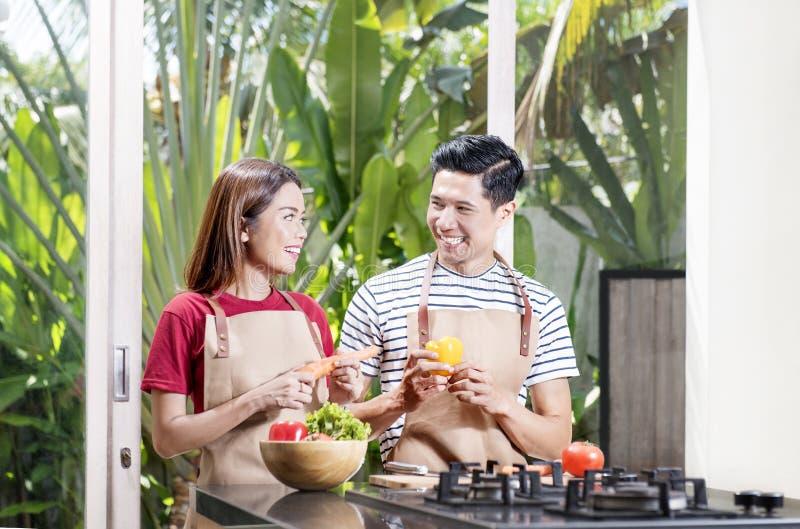 Счастливые азиатские пары подготавливая свежие овощи для варить стоковые фото