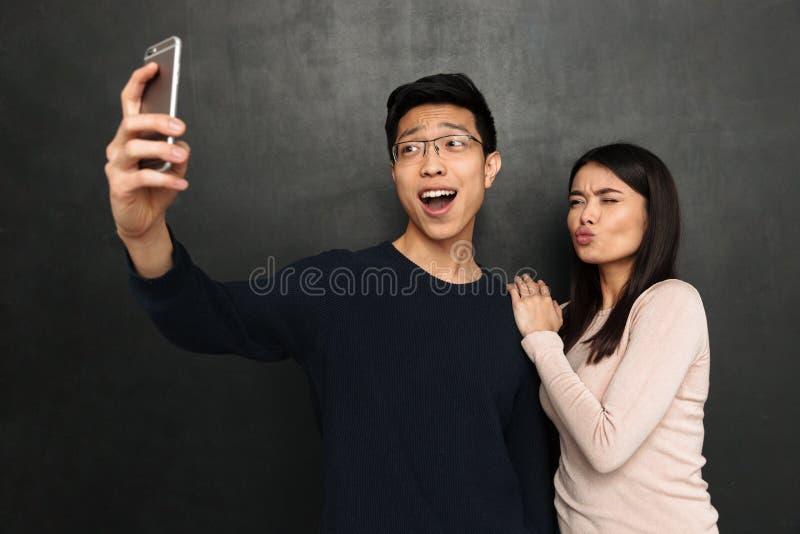 Счастливые азиатские пары представляя совместно и делая selfie на smartphone стоковые изображения rf