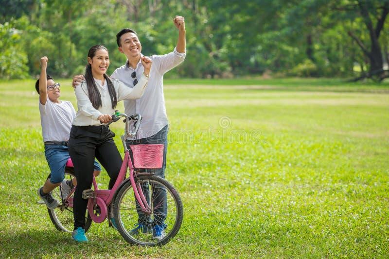 счастливые азиатские семья, родители и дети ехать руки велосипеда вверх в парке совместно отец, мать, сын на велосипеде имея поте стоковые изображения rf