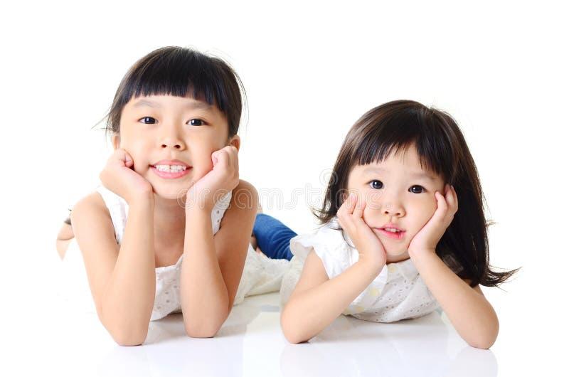 Счастливые 2 азиатских девушки на белой предпосылке стоковое изображение