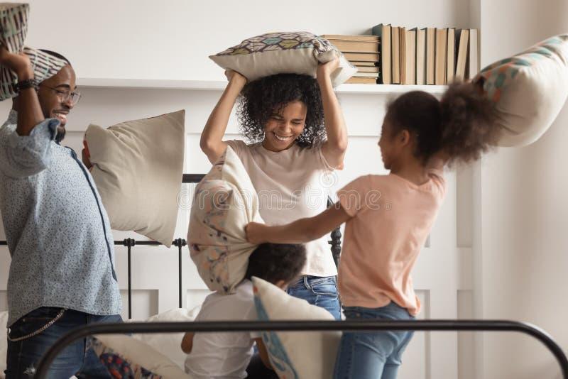 Счастливые африканские родители и дети имея бой подушками на кровати стоковые фотографии rf