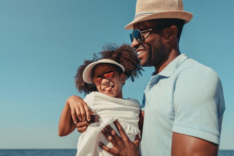 счастливые Афро-американские отец и дочь в солнечных очках имея потеху совместно стоковая фотография