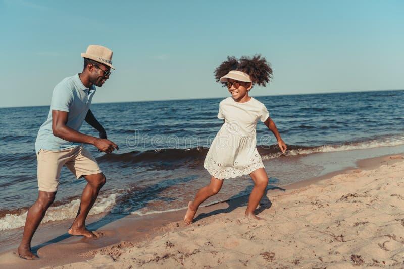 счастливые Афро-американские отец и дочь в солнечных очках имея потеху пока играющ совместно стоковое изображение