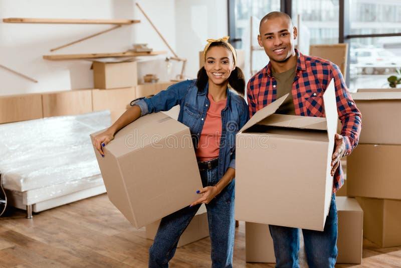 счастливые Афро-американские пары держа картонные коробки и двигая к стоковая фотография rf