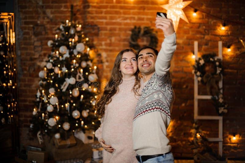 Счастливые беременные пары делая selfie на предпосылке рождественской елки стоковая фотография