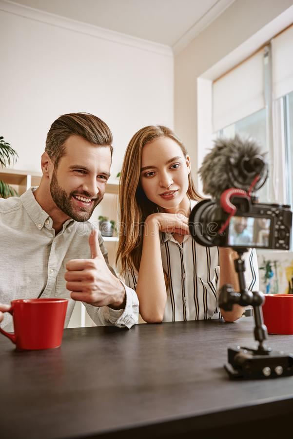 Счастливые блоггеры Пары положительных блоггеров записывая новое видео для их блога, бородатый человека показывая большие пальцы  стоковое фото rf