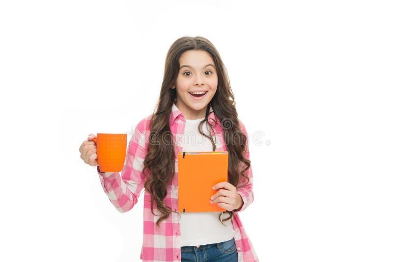 Счастливые блокнот владением ребенка и чашка чая подготавливайте для чтения маленькая дама дела E удивленное gorl школы стоковые фото