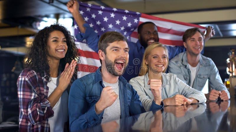 Счастливые болельщики держа флаг Америки, празднуя победу национальной команды стоковое изображение rf