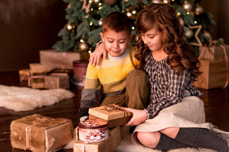 Счастливые брат и сестра детей рассматривают подарки, стоковая фотография