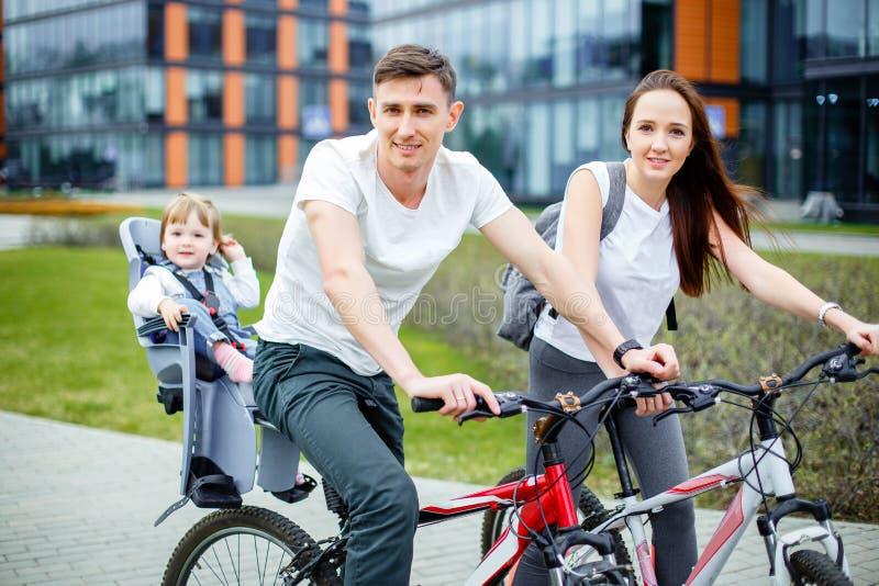 Счастливые велосипеды катания семьи в городе стоковое изображение rf