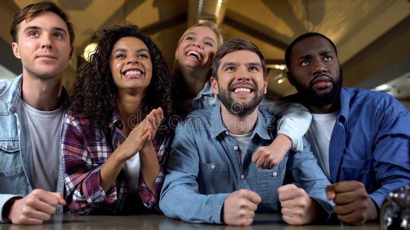 Счастливые вентиляторы команды наблюдая национальный чемпионат, ободрение победы, поддержку стоковое изображение