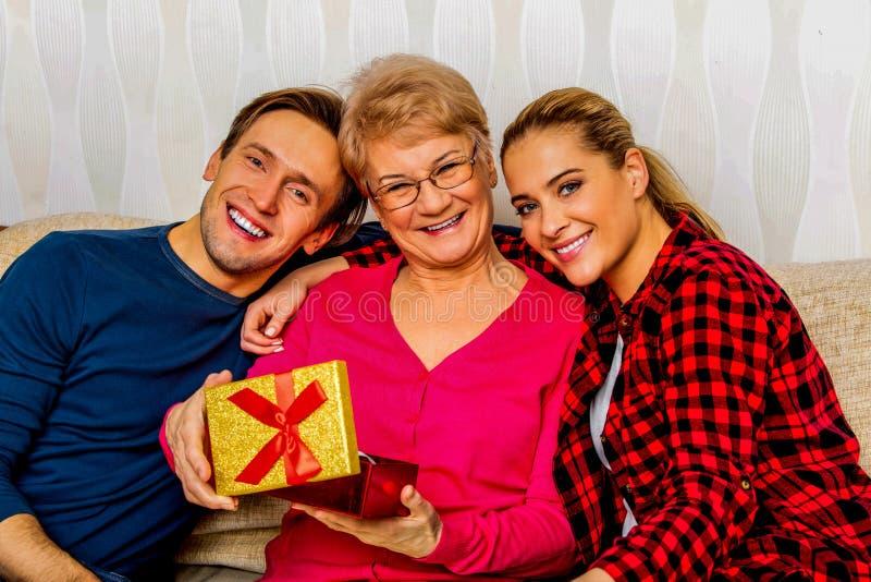 Счастливые взрослые дети с пожилой матерью на кресле стоковые фото