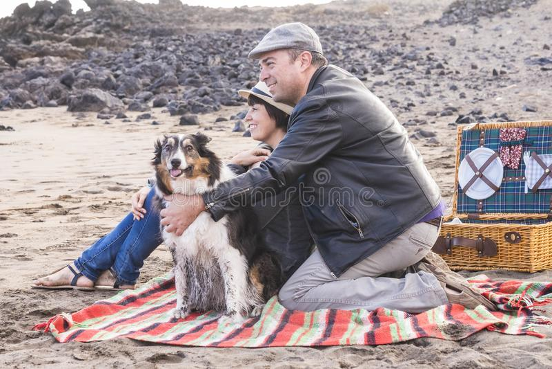 Счастливые взрослые люди семьи остаются совместно на пляже с прелестной смешной грязной собакой - счастьем и на открытом воздухе  стоковые фотографии rf