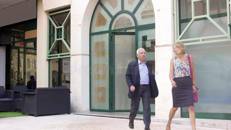 Счастливые взрослые пары покидая ресторан, удовлетворяемый с обслуживанием, бизнес-ланч стоковое фото