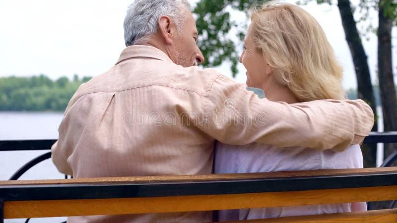 Счастливые выбытые пары ослабляя на скамейке в парке, наслаждаясь выходными снаружи, любовь стоковые изображения rf
