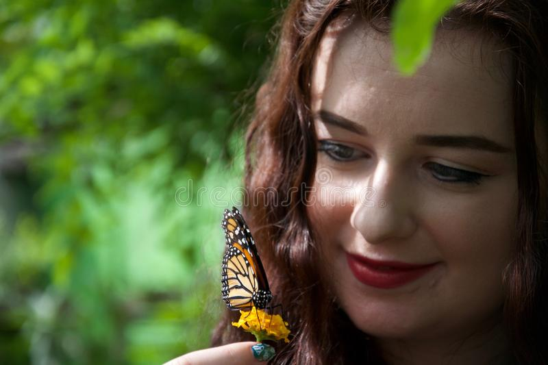 Счастливые дама/девушка держа цветок с бабочкой сидя на ей стоковое фото rf