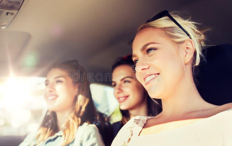 Счастливые девочка-подростки или молодые женщины управляя в автомобиле стоковое фото