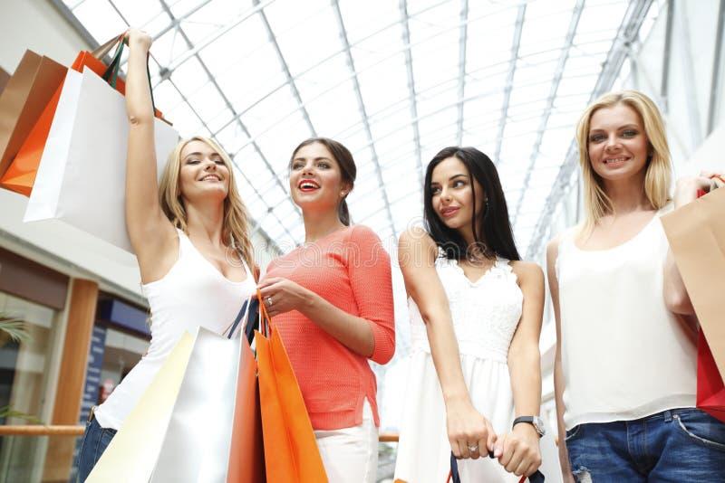 Счастливые девушки в торговом центре стоковые изображения