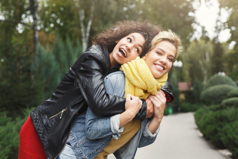 Счастливые девушки имея потеху пока идущ в парке стоковые фото