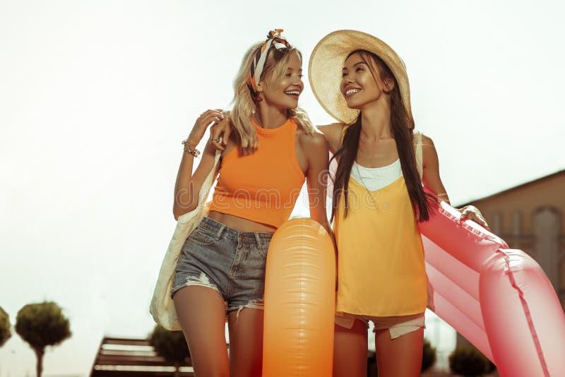 Счастливые девушки обнимая и держа плавая кольца в руках стоковые фото