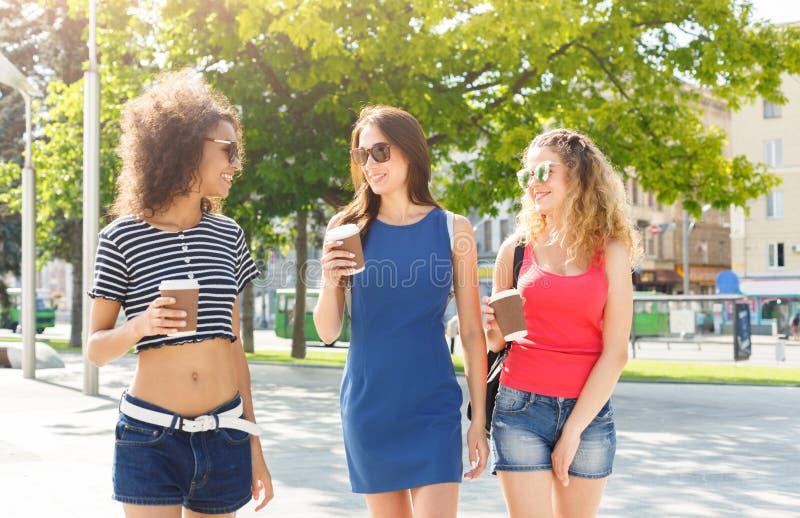 Счастливые девушки с кофе взятия прочь outdoors стоковые фото