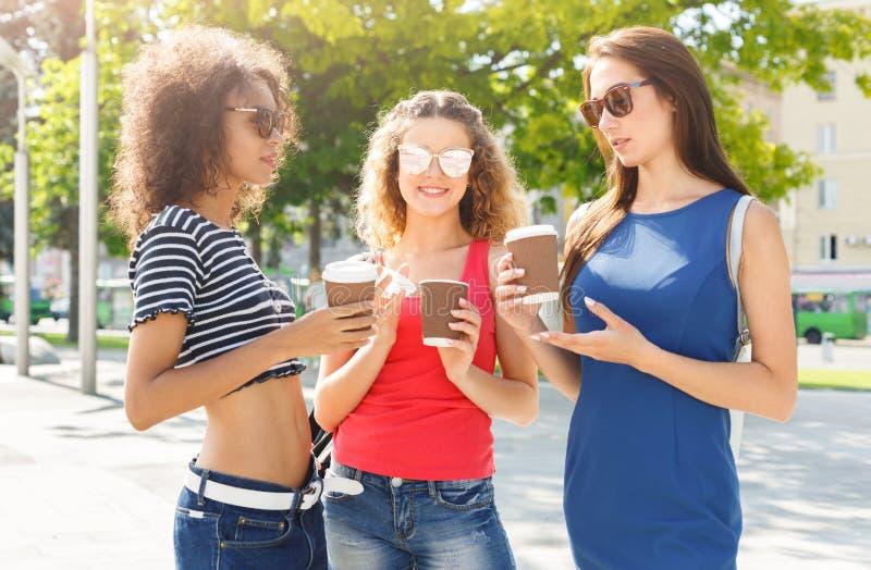 Счастливые девушки с кофе взятия прочь outdoors стоковая фотография rf