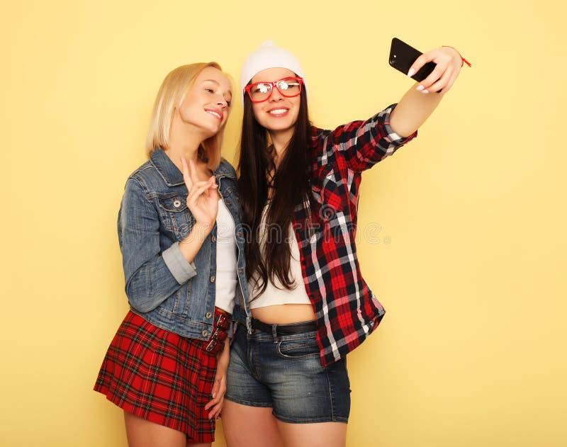 Счастливые девушки с smartphone над желтой предпосылкой Счастливая собственная личность стоковое изображение rf
