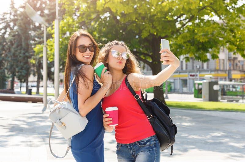 Счастливые девушки с smartphone outdoors в парке стоковое изображение rf