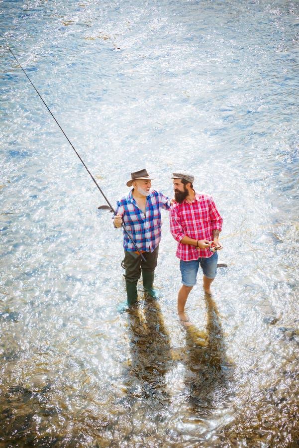 Счастливые дед и внук с рыболовными удочками на койке реки Счастливая концепция семьи - отец и сын совместно Муха стоковая фотография