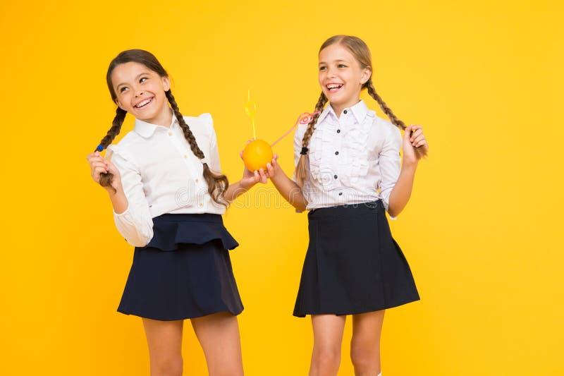 Счастливые дети выпивают сок Питание витамина Школа свежих фруктов Дети девушек выпивая сок оранжевого плода свежий Школьницы стоковое изображение