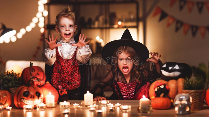 Счастливые дети в костюмах ведьмы и вампира в темном доме стоковые фотографии rf
