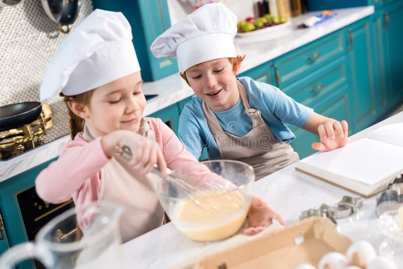 счастливые дети в шляпах шеф-повара делая тесто стоковая фотография rf