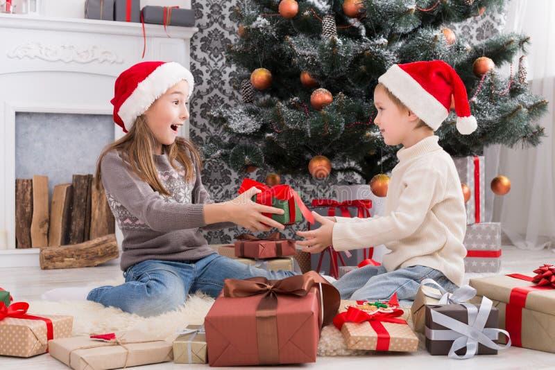 Счастливые дети в шляпах santa развертывая подарки на рождество стоковые фотографии rf