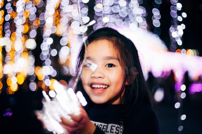 Счастливые дети держат свет в канун Нового года Улица ночного сцены с Рождественскими огнями Концепция Рождественского вечера стоковое фото rf
