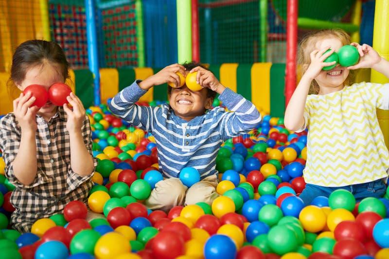 Счастливые дети играя в яме шарика стоковое изображение rf
