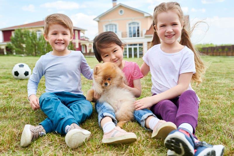 Счастливые дети играя с щенком стоковое фото rf