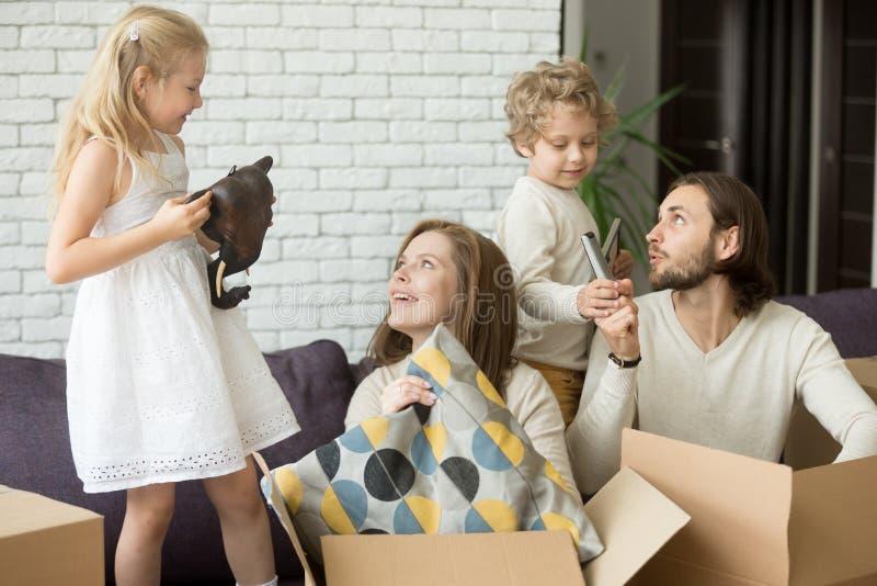 Счастливые дети помогая родителям распаковать коробки на moving день стоковое фото rf