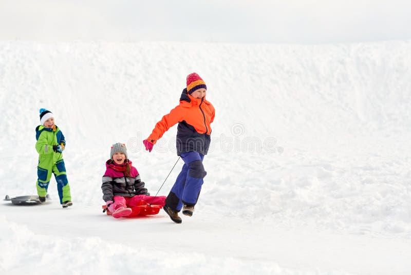 Счастливые дети при скелетон имея потеху outdoors в зиме стоковая фотография