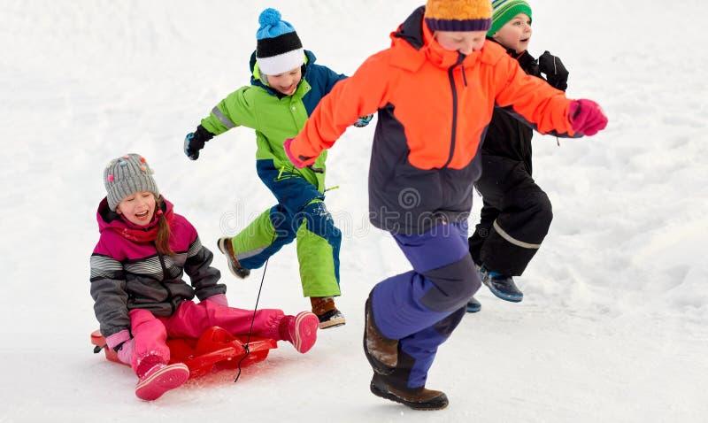 Счастливые дети при скелетон имея потеху outdoors в зиме стоковое фото rf