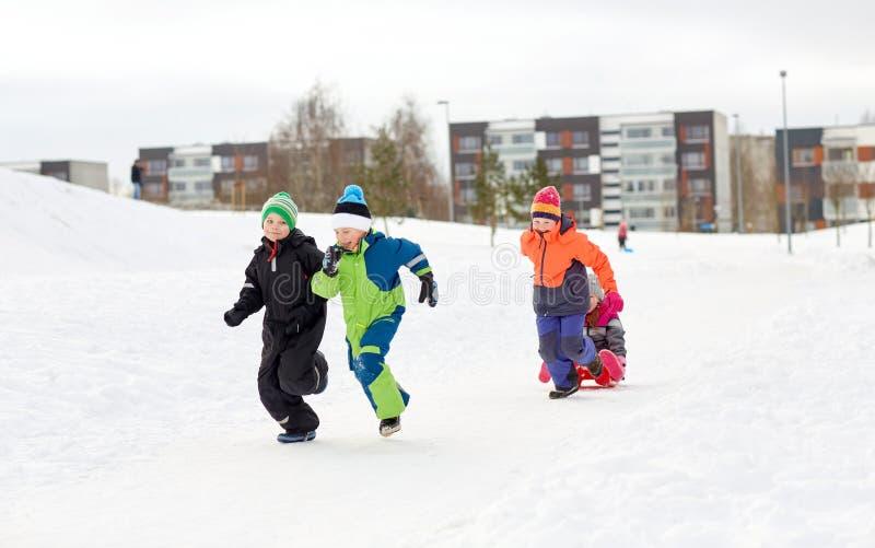 Счастливые дети при скелетон имея потеху outdoors в зиме стоковое фото
