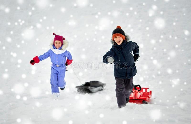 Счастливые дети при скелетон имея потеху outdoors в зиме стоковое изображение
