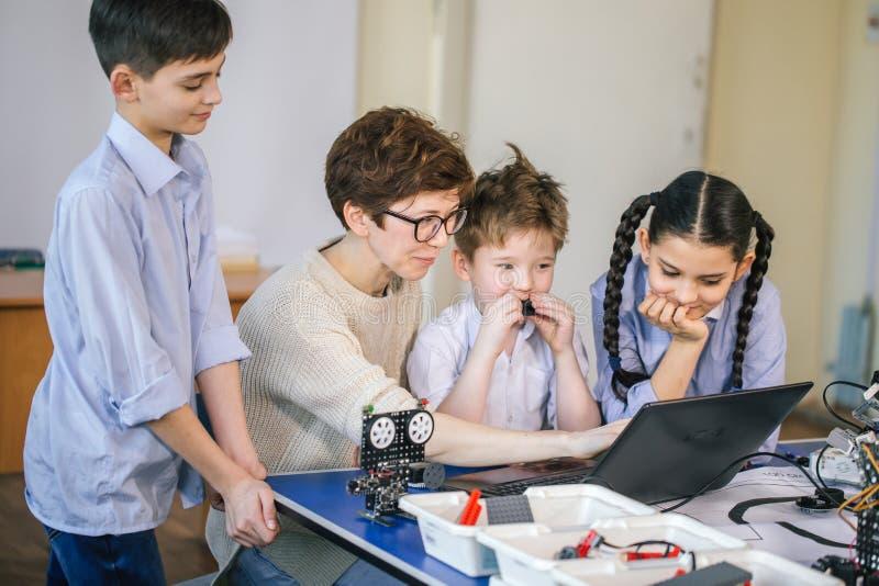 Счастливые дети учат программирование используя компьтер-книжки на внеучебных классах стоковые изображения