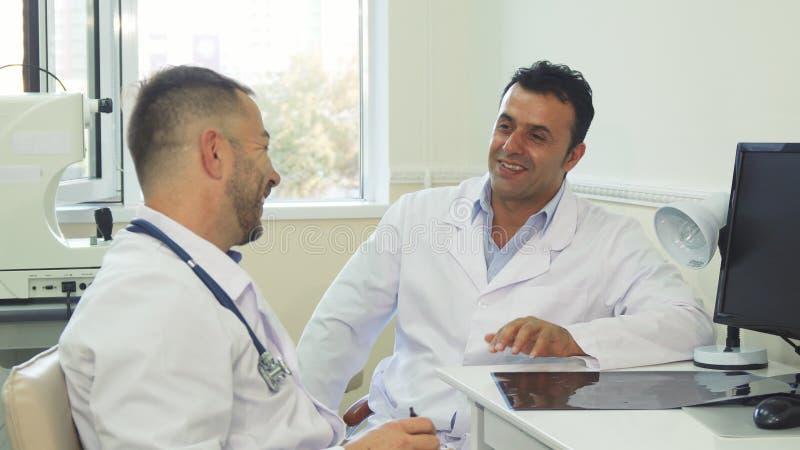 Счастливые доктора обсуждают что-то и смеются над стоковые фото