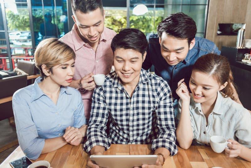 Счастливые друзья в кафе смотря цифровой планшет стоковая фотография