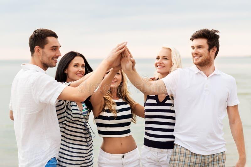 Счастливые друзья делая высоко 5 на пляже стоковая фотография rf