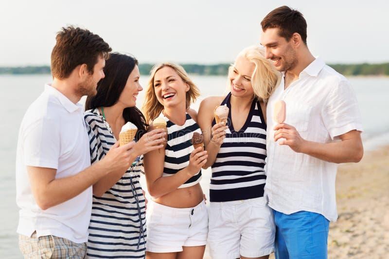 Счастливые друзья есть мороженое на пляже стоковое изображение