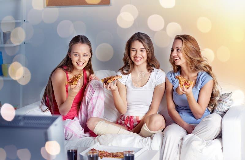 Счастливые друзья есть пиццу и смотря ТВ дома стоковое изображение rf